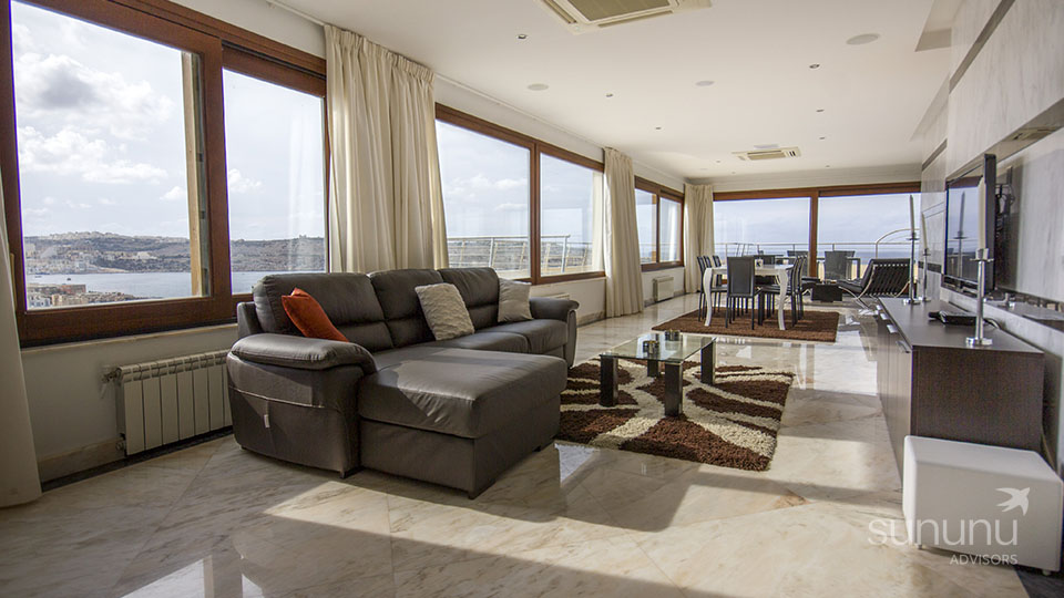 Sprawling living/dining area of penthouse in St. Paul's Bay, with gorgeous views