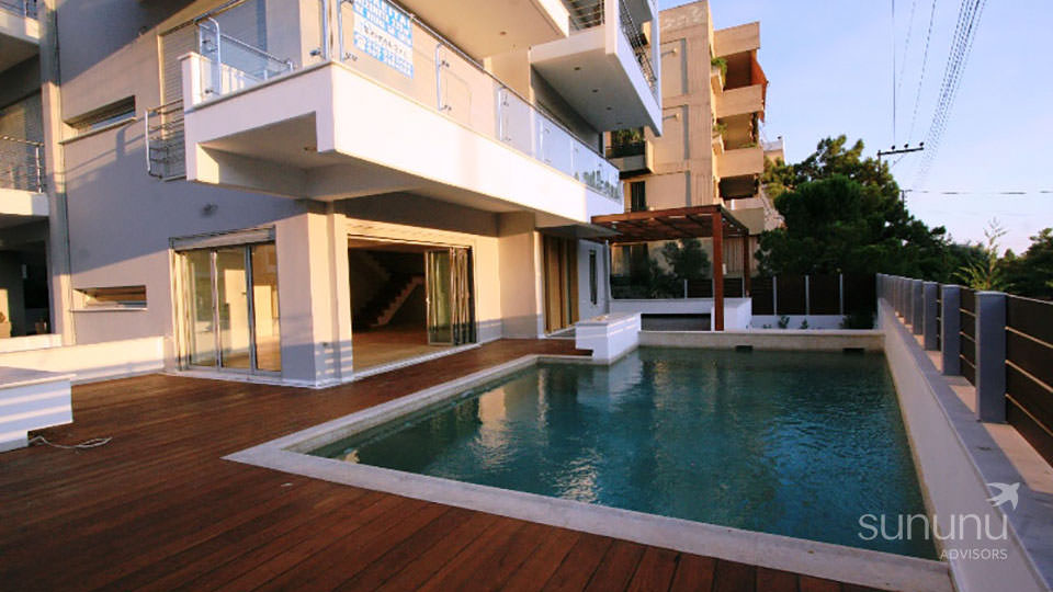 Swimming pool, wooden deck and modern exterior of maisonette in Glyfada